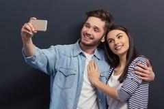 Pares novos com dispositivo Fotografia de Stock Royalty Free