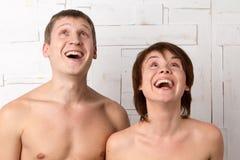 Pares novos com emoções da alegria perto da parede branca Fotografia de Stock