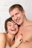 Pares novos com emoções da felicidade perto da parede branca Fotos de Stock Royalty Free