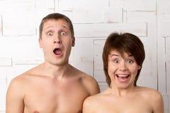 Pares novos com emoções da maravilha perto da parede branca Foto de Stock Royalty Free