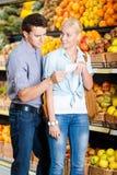 Pares novos com lista de compra contra os montões dos frutos Fotografia de Stock