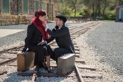 Pares novos com a mala de viagem do vintage nos trainlines prontos para a Fotografia de Stock Royalty Free