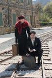 Pares novos com a mala de viagem do vintage nos trainlines prontos para a Foto de Stock