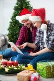 Pares novos com o GIF em linha de compra do Natal dos chapéus de Santa Claus Fotografia de Stock Royalty Free