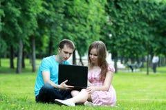 Pares novos com o portátil no parque Foto de Stock Royalty Free