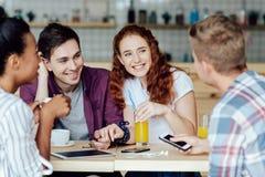 Pares novos com os amigos no café fotografia de stock royalty free
