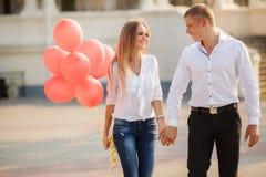 Pares novos com os balões coloridos na cidade Fotos de Stock Royalty Free