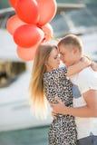 Pares novos com os balões coloridos na cidade Fotografia de Stock