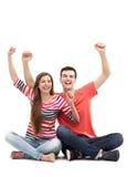 Pares novos com os braços aumentados Fotografia de Stock Royalty Free