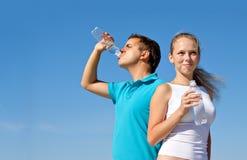 Pares novos com os frascos da água Fotografia de Stock Royalty Free