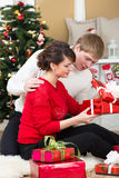 Pares novos com os presentes na frente da árvore de Natal Foto de Stock Royalty Free