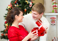 Pares novos com os presentes na frente da árvore de Natal Imagem de Stock Royalty Free