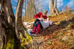 Pares novos com roupa tradicional na floresta natural - amor e sol imagens de stock