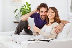 Pares novos com tabuleta digital em casa Fotos de Stock Royalty Free
