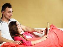 Pares novos com tabuleta e cartão de crédito em casa Foto de Stock