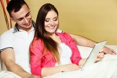 Pares novos com a tabuleta que senta-se no sofá em casa Imagens de Stock