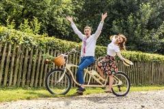 Pares novos com tandem da bicicleta no parque Os jovens mantêm chapéus em seus mãos e sorriso Na parte de trás da cerca da árvore Imagem de Stock