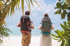 Pares novos com a trouxa grande que anda à praia em um destino tropical do feriado fotografia de stock