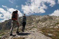 Pares novos com a trouxa grande que anda para alcançar a parte superior da montanha durante um dia ensolarado imagens de stock royalty free