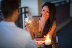 Pares novos com um jantar romântico com velas Imagem de Stock
