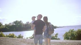 Pares novos com uma criança que anda para o rio, guardando as mãos filme