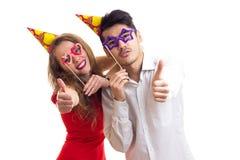 Pares novos com varas do cartão e chapéus da comemoração Imagem de Stock Royalty Free