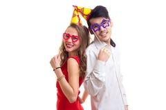 Pares novos com varas do cartão e chapéus da comemoração Fotos de Stock Royalty Free