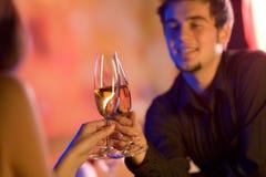 Pares novos com vidros do champanhe no restaurante Imagem de Stock