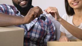 Pares novos da família com as caixas de cartão que mostram a chave do apartamento novo, movendo-se filme