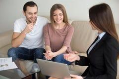 Pares novos da família com o corretor fêmea que discute a hipoteca, suporte foto de stock royalty free