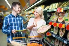 Pares novos da família que escolhem a pizza refrigerada Imagem de Stock Royalty Free
