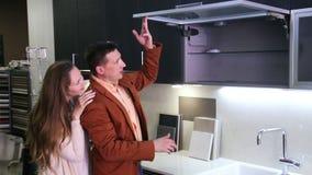 Pares novos da família que olham a cozinha moderna na loja vídeos de arquivo