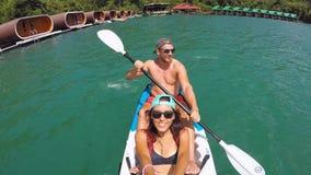 Pares novos da raça misturada que kayaking no lago Selfie ativo slowmotion do gopro do estilo de vida de HD filme