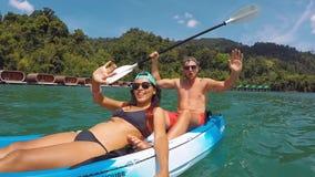 Pares novos da raça misturada que kayaking no lago Selfie ativo slowmotion do gopro do estilo de vida de HD video estoque