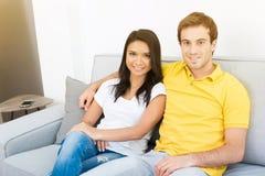 Pares novos da raça misturada que sentam-se no sofá imagem de stock