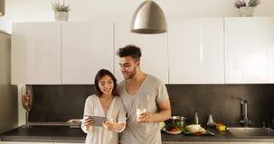 Pares novos da raça misturada usando a luz solar da manhã do tablet pc, mulher asiática do homem latino-americano feliz junto na
