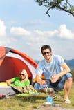 Pares novos de acampamento com o campo do cozinheiro da barraca Imagens de Stock Royalty Free