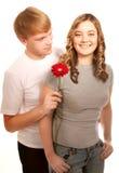 Pares novos de amantes. O homem apresenta a flor. Dia de são valentim imagem de stock