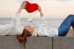 Pares novos de amantes que encontram-se no parapeito de pedra Fotografia de Stock