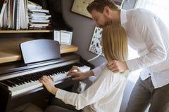 Pares novos de amor que jogam o piano foto de stock royalty free