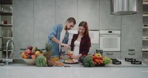 Pares novos de canto e dacing na manhã em sua cozinha moderna ao cozinhar o café da manhã na manhã video estoque