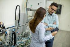 Pares novos de estudantes que trabalham no laboratório da robótica imagem de stock