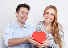 Pares novos de riso do amor com um presente Imagens de Stock