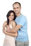 Pares novos de sorriso que estão junto, abraçando Fotografia de Stock Royalty Free