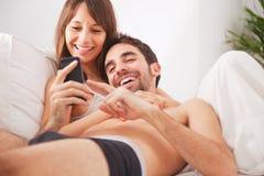 Pares novos de sorriso que olham o smartphone na cama fotografia de stock