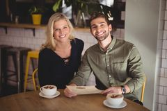 Pares novos de sorriso que sentam-se com copos e menu de café na tabela Fotos de Stock Royalty Free