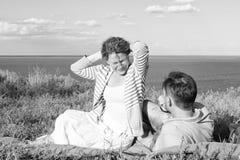Pares novos de sorriso que sentam-se na grama próximo da água Equipe a colocação na grama que olha na mulher feliz do cabelo verm foto de stock royalty free