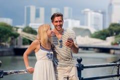 Pares novos de turista que usa o telefone celular fotografia de stock royalty free