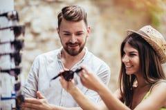 Pares novos de turistas que compram óculos de sol novos na tenda de rua exterior imagem de stock