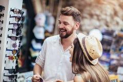Pares novos de turistas que compram óculos de sol novos na tenda de rua exterior fotografia de stock